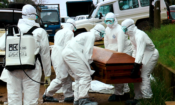 Ebola burial workers in Monrovia disinfect the body of a person who died of Ebola. (Photo by Alexander Wiaplah.)