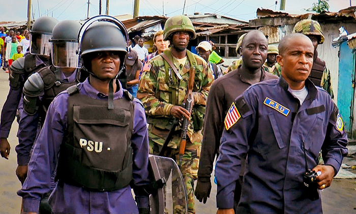 Liberian military and police enforce a quarantine on West Point, one of the poorest slums in Monrovia. (Photo by Alexander Wiaplah.)