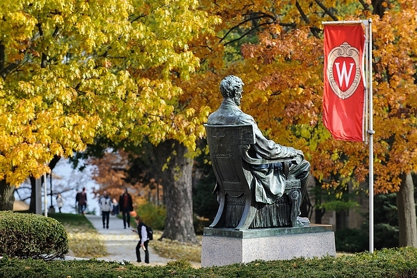 "The Abraham Lincoln statue remains sentinel to the changing seasons on Bascom Hill at the University of Wisconsin-Madison as the tree foliage continues to change colors during autumn on Nov. 8, 2013. In the background, pedestrians walk past one of the ""W"" crest banners on Bascom Hill. (Photo by Jeff Miller/UW-Madison)"