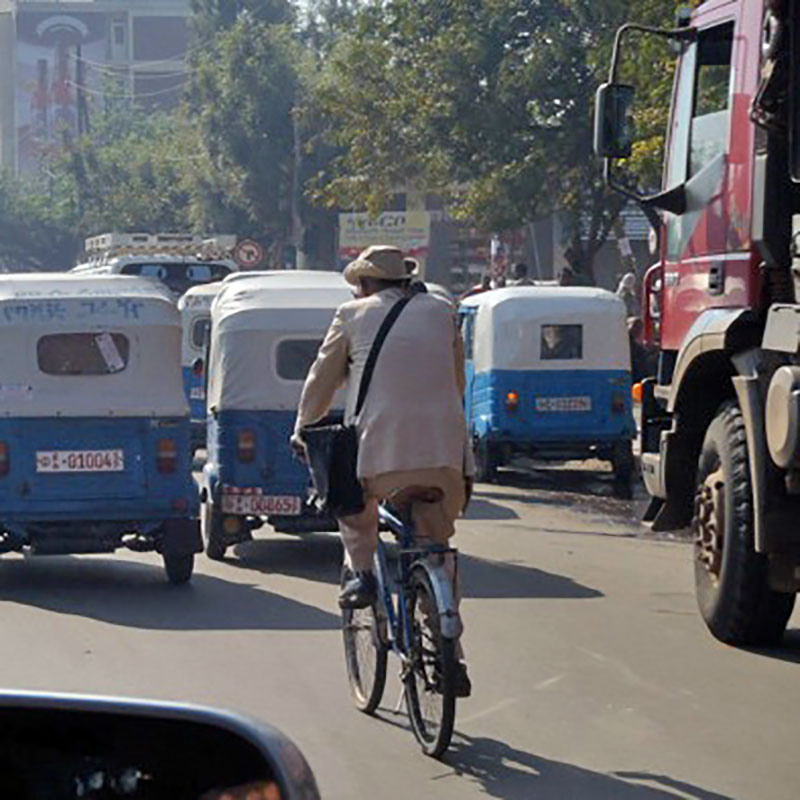 Man biking through crowded street, filled with trucks and small cars