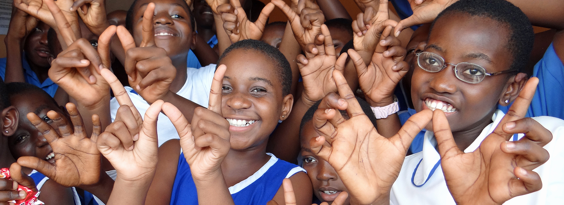 "Smiling children making the letter ""W"" with their fingers"
