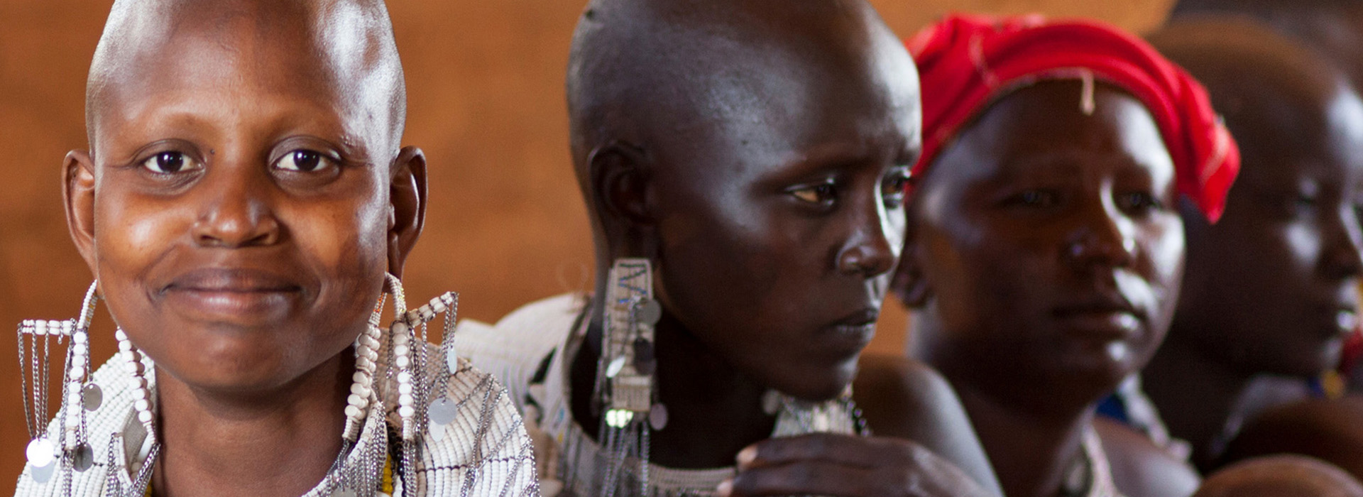 Three African woman proudly display traditional jewelry, especially earrings