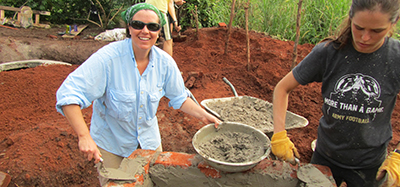 A female UW-Madison student shows the mortar being used to construct a biodigester with a wheelbarrow full of mortar behind her.