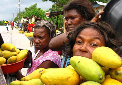 Three women with mangoes at market