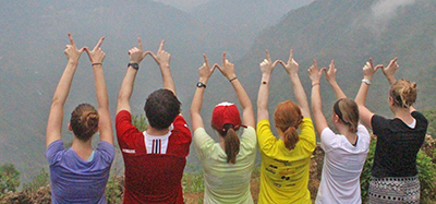 A row of students stand with their hands making W's. They have their backs to us and are facing the mountains of Nepal.