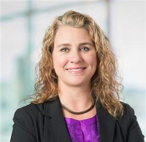 Head shot of Dr. Janna Patterson with long curly hair, a black suit jacket and purple blouse.
