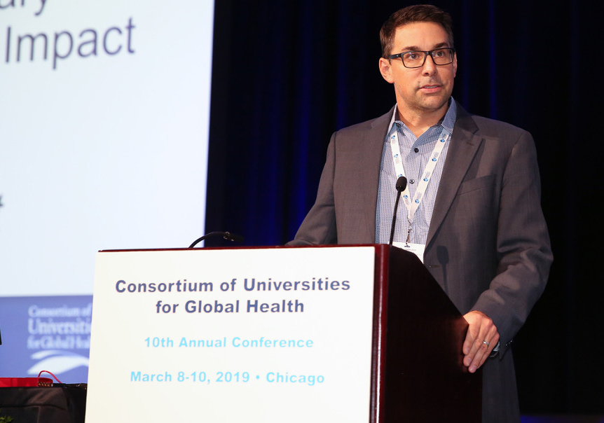 Janis Tupesis stands behind a podium at the Consortium of Universities for Global Health conference.