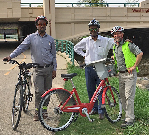 three men stand together with their bicycles