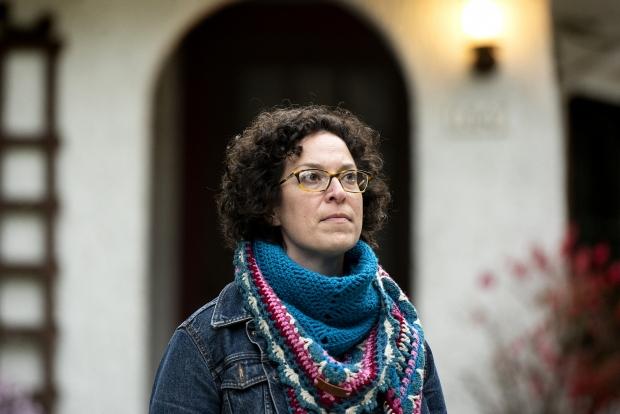 a woman stands in front of her doorway.