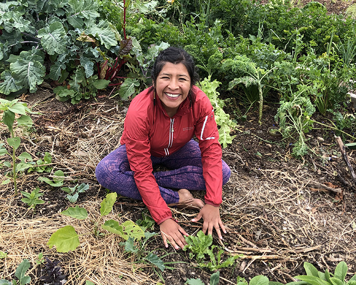 Mariaelena Huambachano sits and works in a New Zealand garden