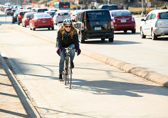 A woman rides her bike in the bike lane.